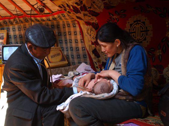 Un médico comunitario vacuna a una madre y su hijo en Mongolia, dentro de una programa de salud maternal y posnatal.
