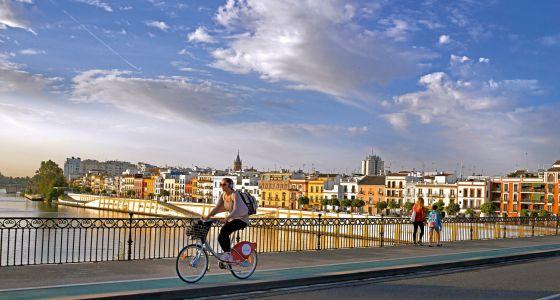 Una joven cruza el puente de Isabel II en una de las bicicletas del servicio público.