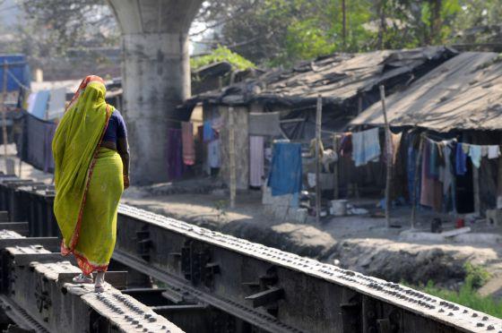 Una mujer cruza un improvisado puente en una barriada de chabolas de Calcuta.