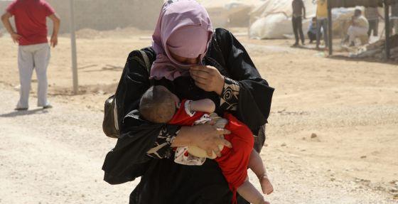 Una refugiada siria lleva a su hijo en brazos mientras camina entre una tormenta de arena en Mafraq (Jordania).