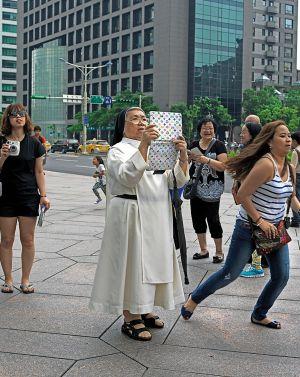 Una monja con una tableta a los pies del Taipéi.