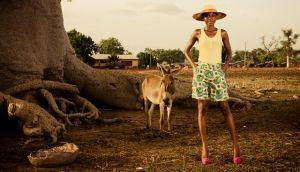 Una modelo de pie junto a un baobab.