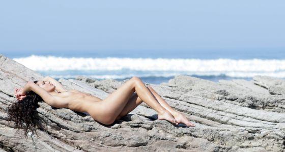 Mujer ejerciendo la arcaica práctica de tomar el sol sin marcas de ropa