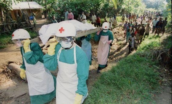 Miembros de la Cruz Roja transportan el cadáver de una víctima de ébola, en 1995, cerca de Kikwit, en Zaire.