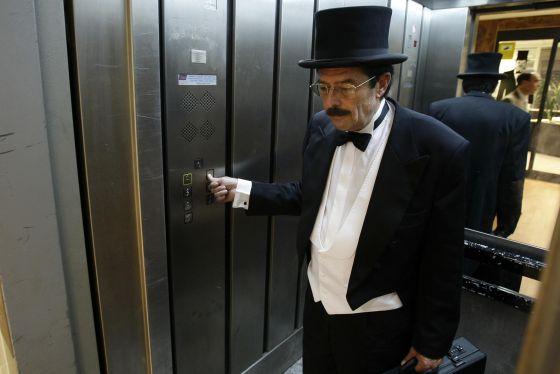 Un trabajador de la empresa Cobrador del Frac en un ascensor madrileño en 2008