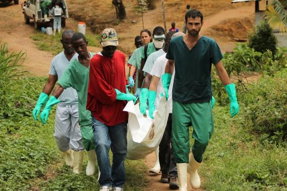 Personal de MSF y familiares entierran a un fallecido por ébola en Liberia