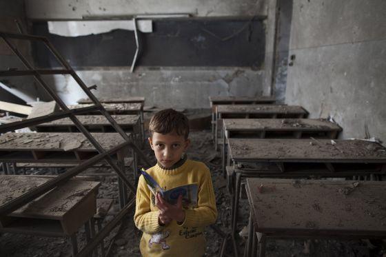 Ali, de 9 años, posa en su escuela, destruida por un bombardeo, en Alepo.