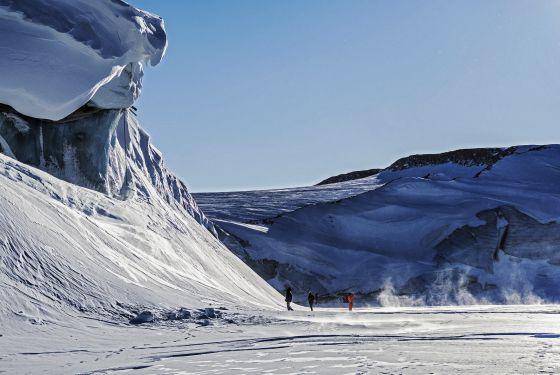 Científicos de la Operación IceBridge, este verano, frente al muro de hielo que es el frente del glaciar Great Land. NASA  Michael Studinger