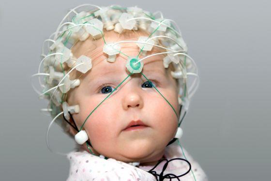 Um bebê de seis meses com um capacete de eletrodos para registrar sua atividade cerebral.