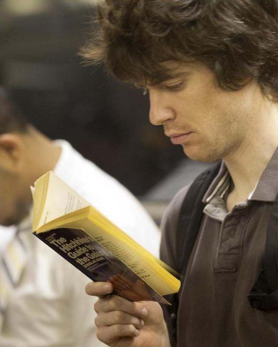 Hombre leyendo 'Guía para el autoestopista galáctico', de Douglas Adams