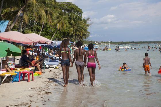 Tres jóvenes pasean por la playa de Boca Chica.