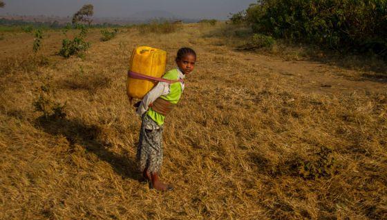 Una niña etíope carga con un contenedor de agua en su espalda.