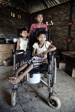 Nu Kai posa en su vivienda con sus hermanos. La metralla le dañó la espina dorsal y ahora tanto ella como su hermana mayor han tenido que dejar de acudir a la escuela para cuidar de ella y ahorrar con el objetivo de pagar las operaciones que requiere.