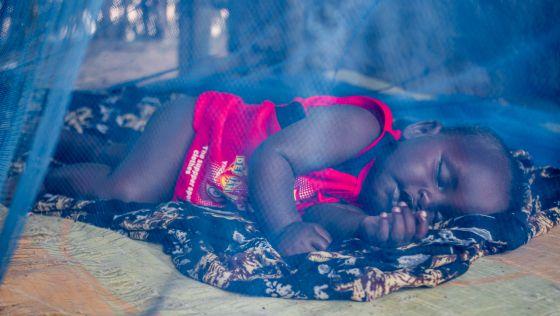 Un bebé nacido en Dadaab duerme sobre el suelo de su casa, protegido por una mosquitera.