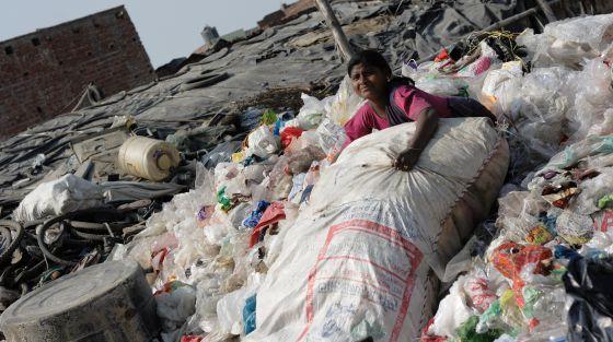 Una niña, entre montones de basura.