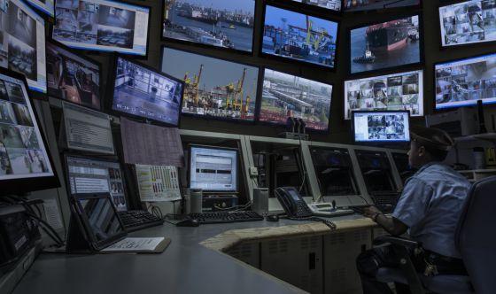 Un guardia de seguridad observa las pantallas de una sala de control.