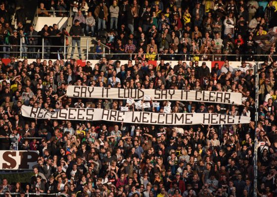 Una pancarta da la bienvenida a los refugiados durante un partido de fútbol en Alemania.