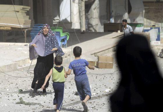 Una mujer corre a por sus hijos tras un bombardeo en Idlib, Siria