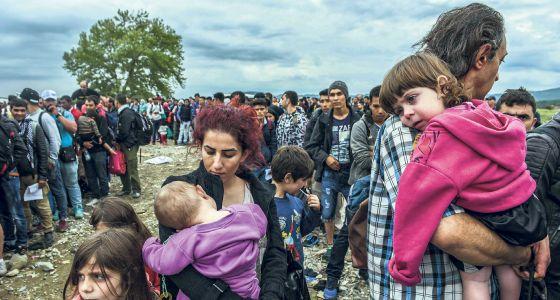 Inmigrantes y refugiados cruzan la frontera de Grecia por Macedonia.