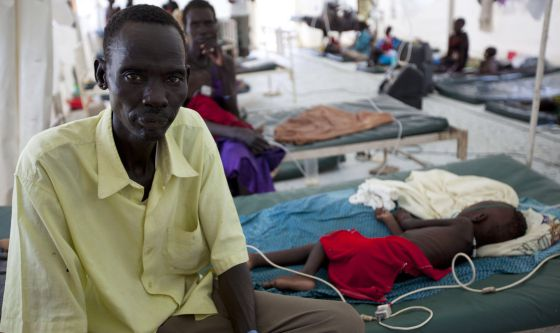 Un hombre junto a su hija, enferma de malaria