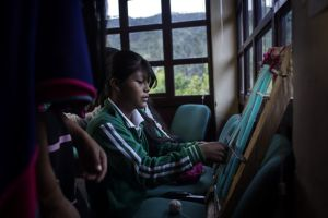 Una niña de etnia misak aprende a tejer en la Casa del Agua.
