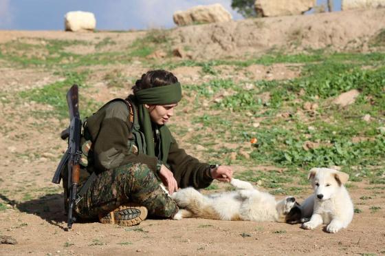 Una combatiente cristiana juega con dos perros en Al-Qahtaniyah (Siria)