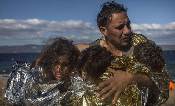 Un hombre sostiene a tres niños que se protegen con mantas térmicas a su llegada a la isla griega de Lesbos el 28 de octubre.