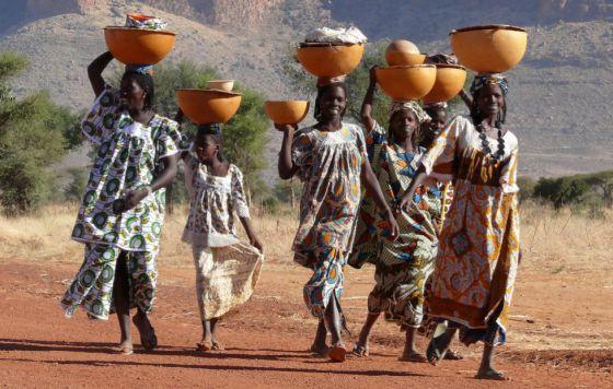 Mujeres de la tribu peul en Mali portan sobre sus cabezas grandes cuencos con ropa y leche.