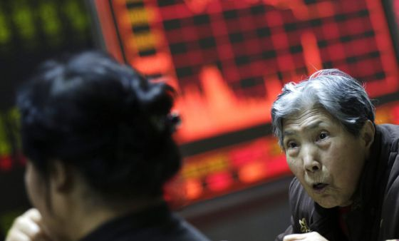 Varios inversores observan la información bursátil en una oficina de corretaje en Pekín