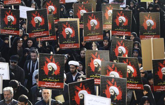 Manifestantes iraníes muestran carteles con el retrato del clérigo y dirigente chií, Nimr Baqir al Nimr, durante una protesta convocada en Teherán (Irán) el lunes.