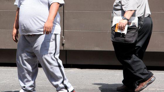 Dos hombres con sobrepeso caminan en Ciudad de México.