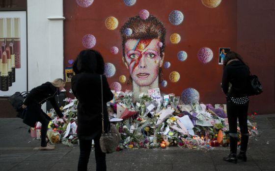 Altar espontáneo junto a un mural dedicado a Bowie en Londres.