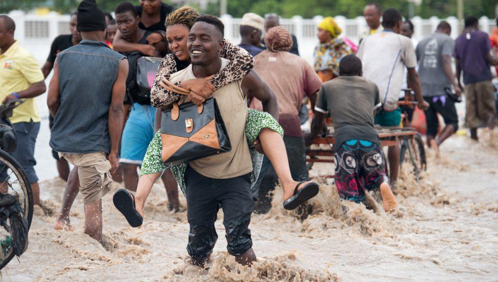 Peatones tratan de cruzar las calles inundadas de Dar es Salaam (Tanzania) en marzo del año pasado.