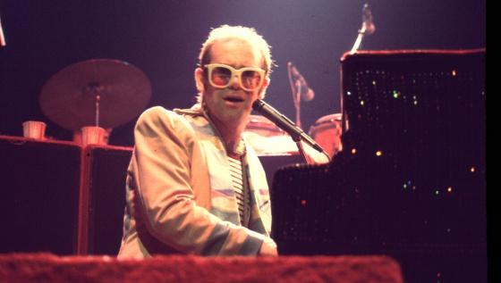 Elton John tenía la cabellera tan despoblada como se ve en este concierto de 1976. Y un buen día apareció con un hermoso peluquín que no se ha vuelto a quitar.
