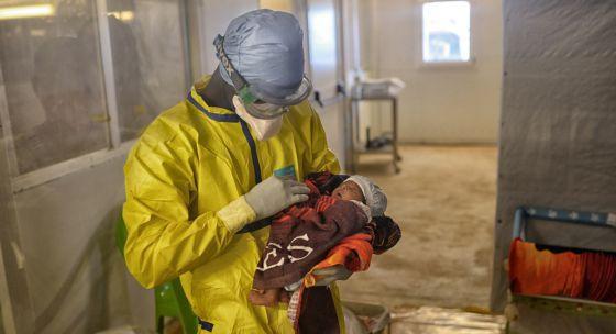 Un trabajador de MSF sostiene a una niña en el centro de tratamiento de ébola de Conakry.