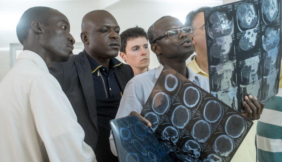 El Profesor Narcisse Zwetyenga y otros compañeros estudian las radiografías de un paciente el día de las consultas para decidir si vale la pena operarle.