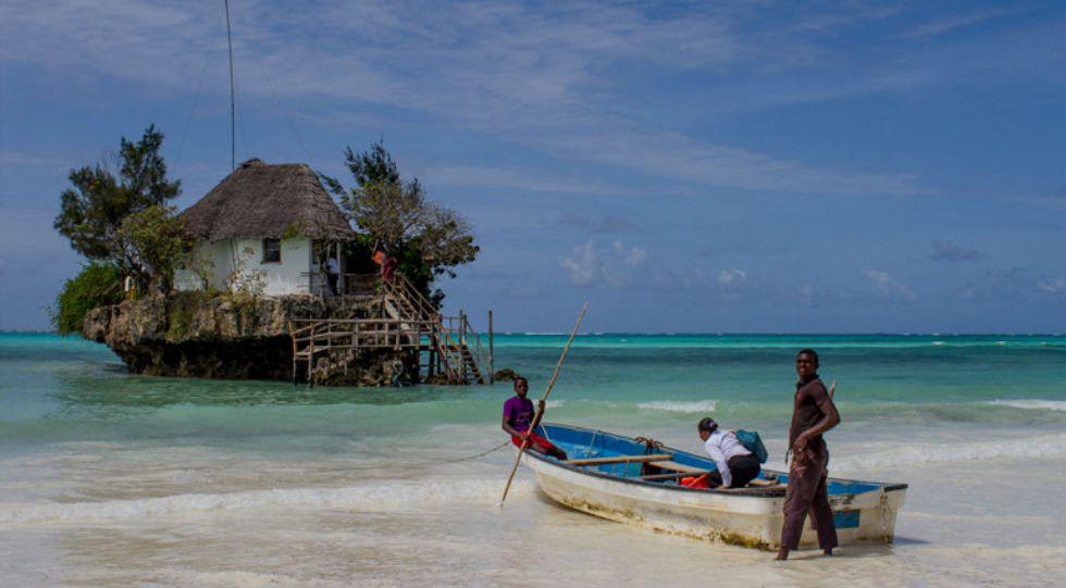 Unos turistas se dirigen en barca al restaurante The Rock de Paje en Zanzibar, Tanzania.