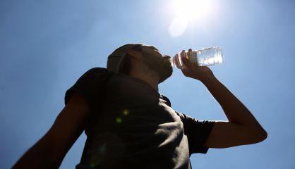 Un joven bebe agua en la puerta del Sol de Madrid.