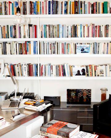 """El despacho de Varoufakis en su casa. Además de su ordenador y un volumen sobre Warhol, en su librería se encuentra una foto junto a su esposa y una pieza de arte satírico con una ilustración de George W. Bush y la leyenda: """"El mayor fracaso de América""""."""