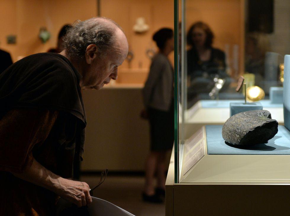 Un hombre observa inscripciones babilónicas en una exposición