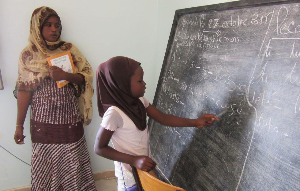 Aisha sale a la pizarra en la escuela para niños víctimas de la esclavitud de Tarhil ante la atenta mirada de su profesora Belly Diallo.