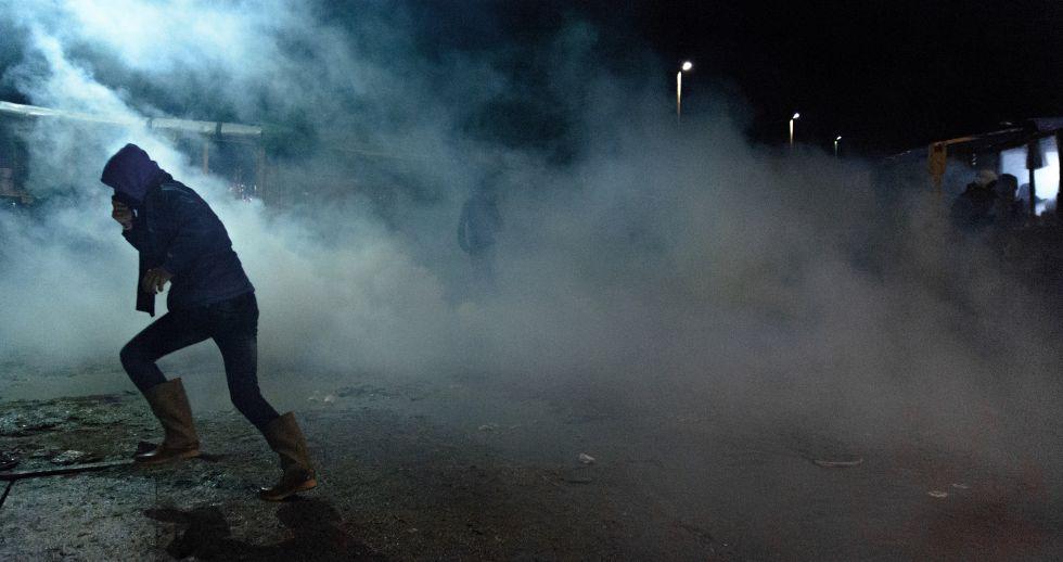 Un refugiado de Calais intenta ponerse a resguardo del gas lacrimógeno.
