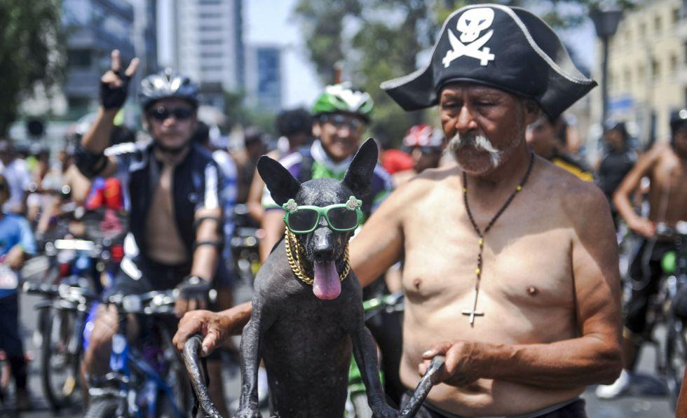Un anciano posa junto con su mascota durante una marcha de ciclistas desnudos en Lima.
