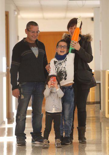 Unai Blanco levanta su brazo artificial, en compañía de sus padres y de una de sus hermanas.