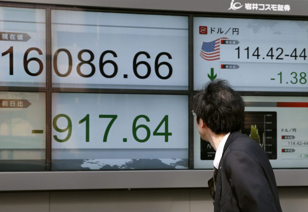 Empresarios caminan junto a pantallas que muestran información bursátil en Tokio.