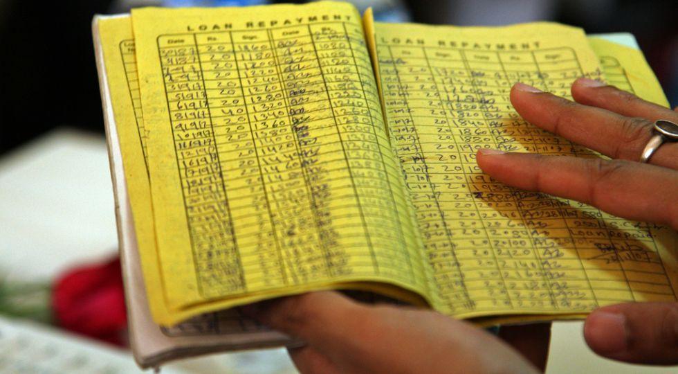 Listado de préstamos y pagos anotados en una libreta.