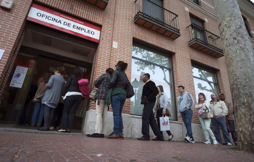Un grupo de personas hacen cola en una oficina del Inem en Alcalá de Henares (Madrid).