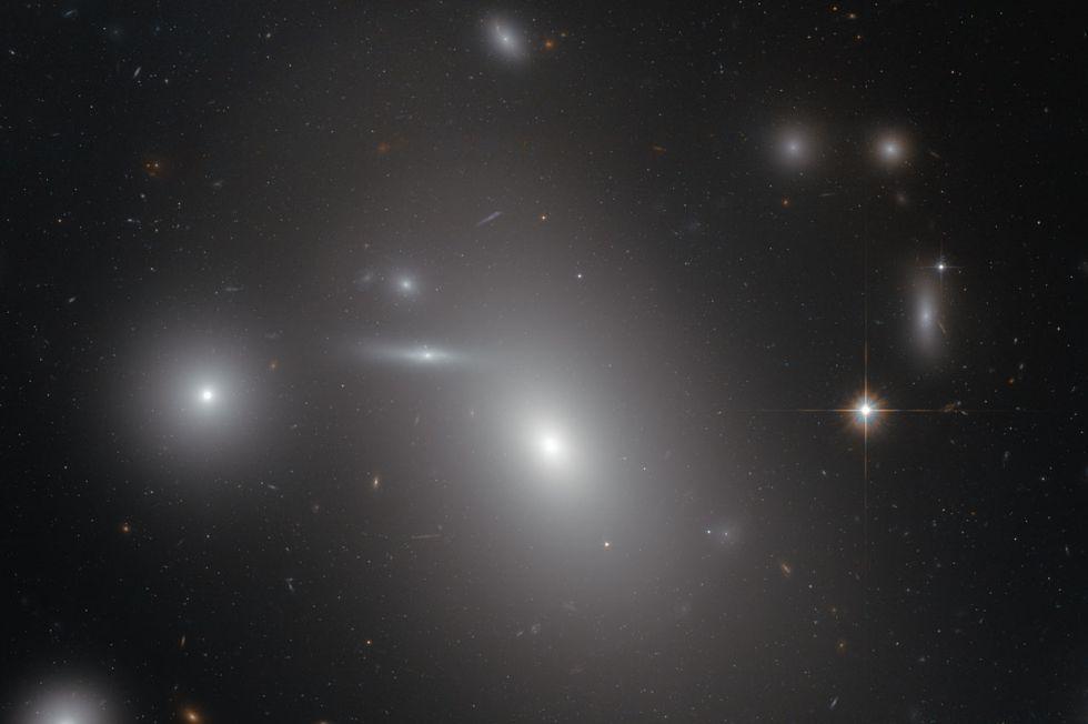 La galaxia elíptica NGC 4889, el objeto más brillante en el centro de la imagen, oculta un descomunal agujero negro en su interior