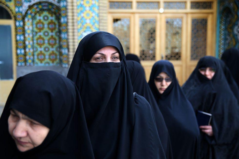 Varias mujeres aguardan para votar en un colegio electoral de la ciudad e Qom.