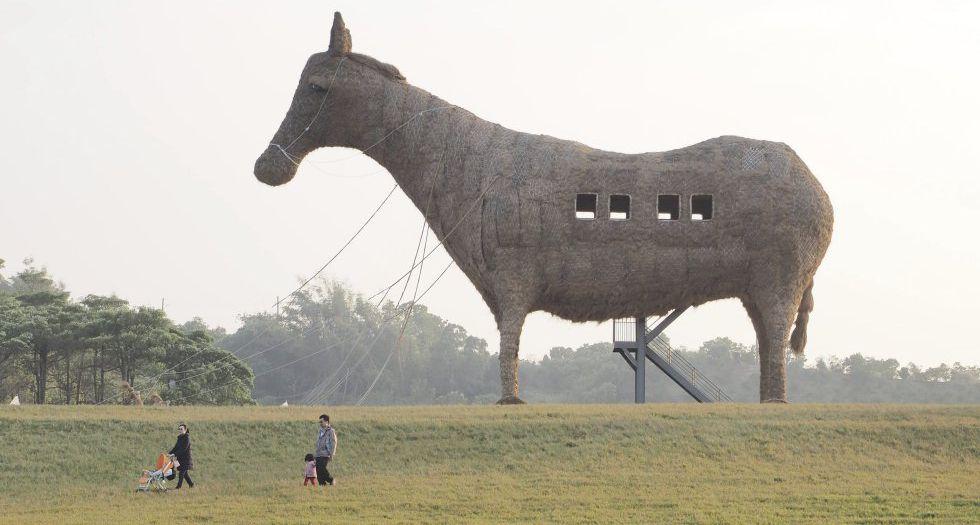 Una familia pasa en el sur de Taiwán junto a un caballo de Troya de 20 metros de alto, 20 de largo y 8 de ancho, esculpido con heno, bambú y acero.